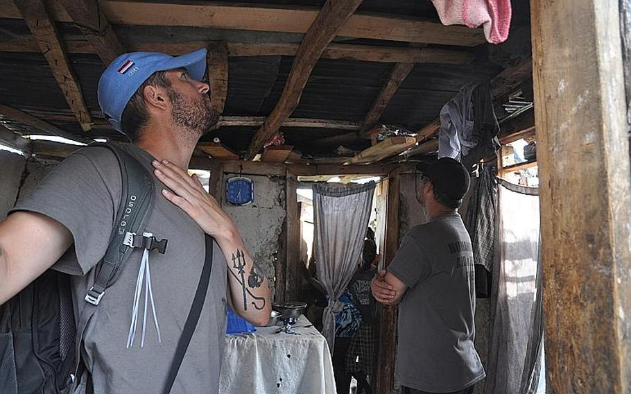 William Gagan, left, and Burke Bryant, right, of the Humanitarian Aid and Rescue Project, inspect a damaged home in the southwest Haiti village of Jabouin on Oct. 18.