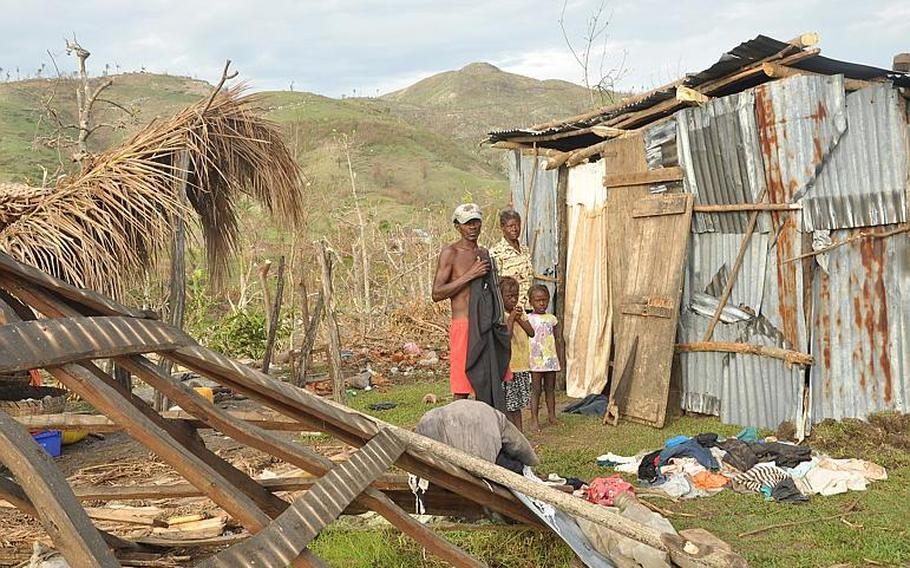 A family in the southwest Haiti village of Jabouin stands on Oct. 18 between their destroyed home to the left and the makeshift shack they cobbled together after Hurricane Matthew left the without shelter.