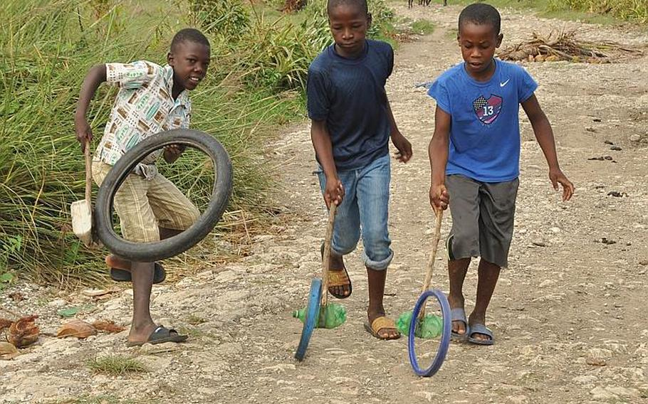 Children play with toys made out of small tires, sticks and empty water bottles in the village of Jabouin in southwest Haiti on Oct. 18. The village was devastated by Hurricane Matthew on Oct. 4.