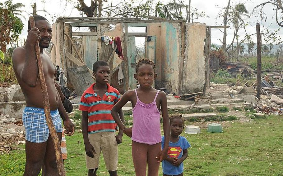 A family stands outside a destroyed home in southwest Haiti on Oct. 18, along the road between the southern coastal city of Les Cayes and the village of Jabouin in the nearby mountains. Hurricane Matthew smacked into the region two weeks ago, leaving an estimated 90 percent of the homes damaged or destroyed. damaged or destroyed.