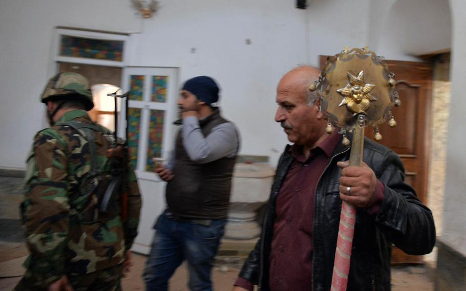 A man carries one of several religious items salvaged from the damaged St. Shmoni Syrian Orthodox Church in the Iraqi town of Bashiqa on Wednesday, Nov. 9, 2016, shortly after anti-Islamic State forces retook the area from militants who had controlled it since 2014.
