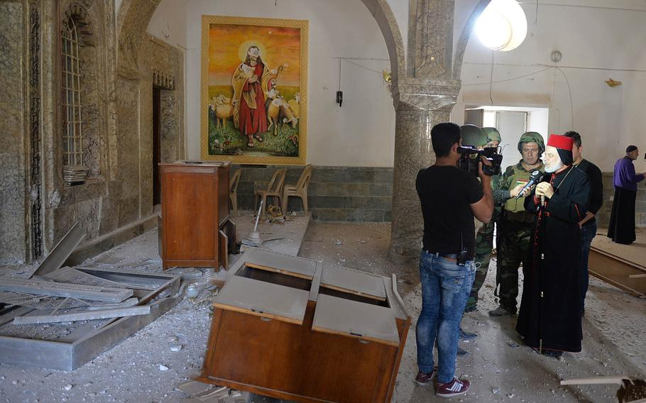 Bishop Mosa Al-Shamani of the Syrian Orthodox Church's diocese in northern Iraq, speaks to a reporter in St. Shmoni Church in Bashiqa, Iraq, on Wednesday, Nov. 9, 2016, shortly after the town was retaken from the Islamic State group that had held it for more than two years.