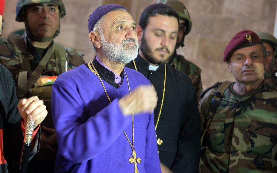 Rev. Aphrem Alkhoury Binyamen makes the sign of the cross while praying at St. George Church in Bahzani, Iraq, about 13 miles from central Mosul, on Wednesday, Nov. 9, 2016. The priest returned to the church for the first time in 2 1/2 years after fleeing the advance of the Islamic State group.