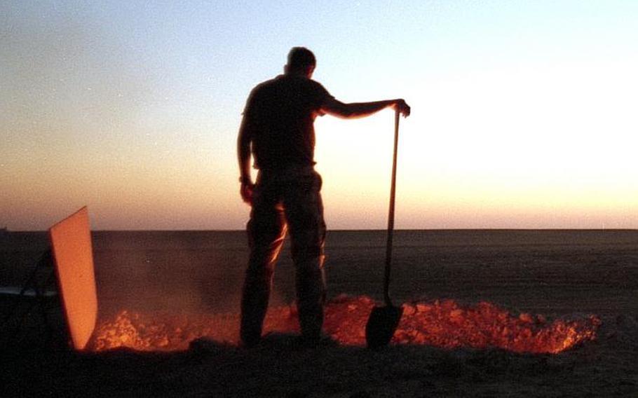 An American servicemember in the Saudi Arabian desert in 1991 tends a burning trash pit.