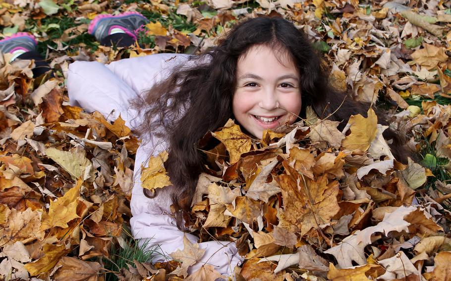 Eliana Adler take a minute to play in the leaves.