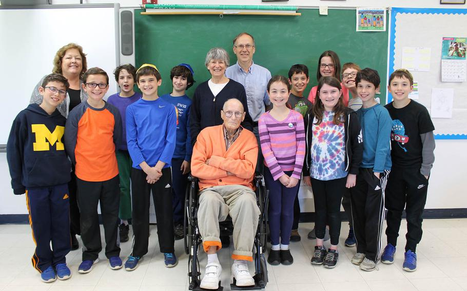 Fifth-graders and their teacher, Carol Gannon, second from left, pose with Mr. Anderson and his family for a group photo.