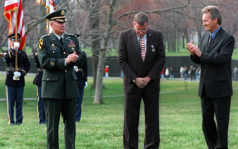 Maj. Gen. Michael Ackerman, left, applauds Hugh Thompson Jr., center, and Lawrence Colburn at the Vietnam Veterans Memorial in Washington Friday, March 6, 1998, during a ceremony where they received the Soldier's Medal. Thirty Years after aiming their weapons at fellow Americans to rescue Vietnamese civilians from the My Lai massacre, the two, along with the late Glenn Andreotta, were finally proclaimed heroes by the Army.