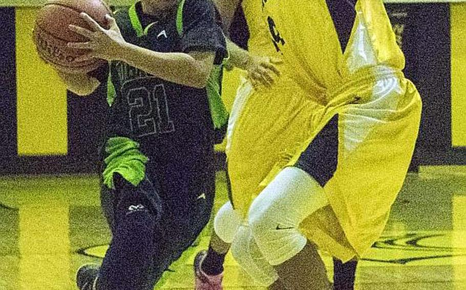 Kubasaki's Dylan Canlas drives against two Kadena defenders during Friday's boys basketball game, won by the two-time defending Far East Division I Tournament champion Dragons 68-62, their first win over the Panthers in four tries this season.