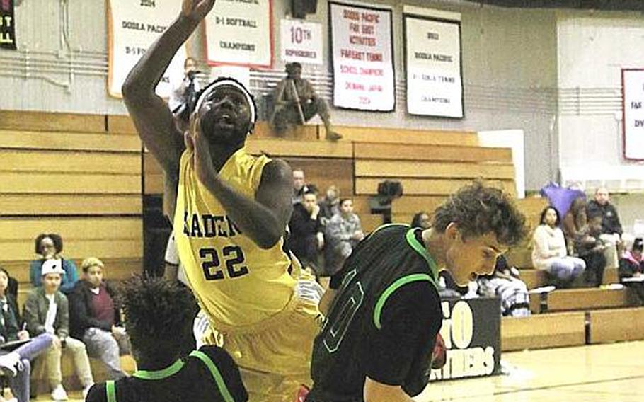 Kadena's Jahron Mitchell rises up for a shot over Kubasaki defenders Xavier Carmouche and Jonathan Hoppe during Friday's boys basketball game, won by the two-time defending Far East Division I Tournament champion Dragons 68-62, their first win over the Panthers in four tries this season.