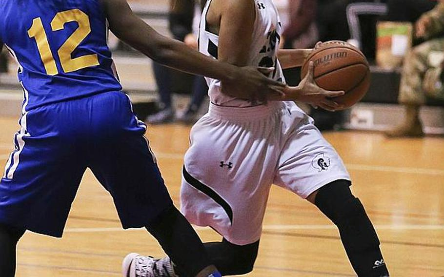 Zama's Ti'Ara Carroll drives past Yokota's Jamia Bailey to the basket during Friday's girls basketball game, won by the Panthers 37-24.