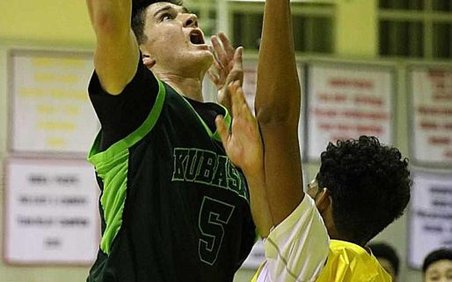 Kubasaki's Bobby Riegert goes up for a shot against Kadena's J.J. Daniels during Friday's boys basketball game, won by the two-time defending Far East Division I Tournament champion Dragons 68-62, their first win over the Panthers in four tries this season.