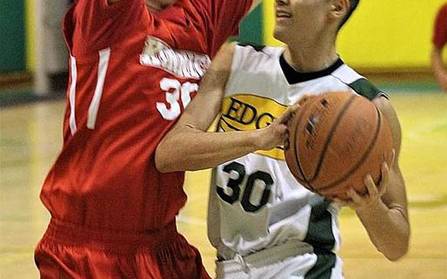 Robert D. Edgren's Roman Perez drives against Nile C. Kinnick's Gage Henderson during Friday's boys basketball game, won by the Red Devils 77-74.