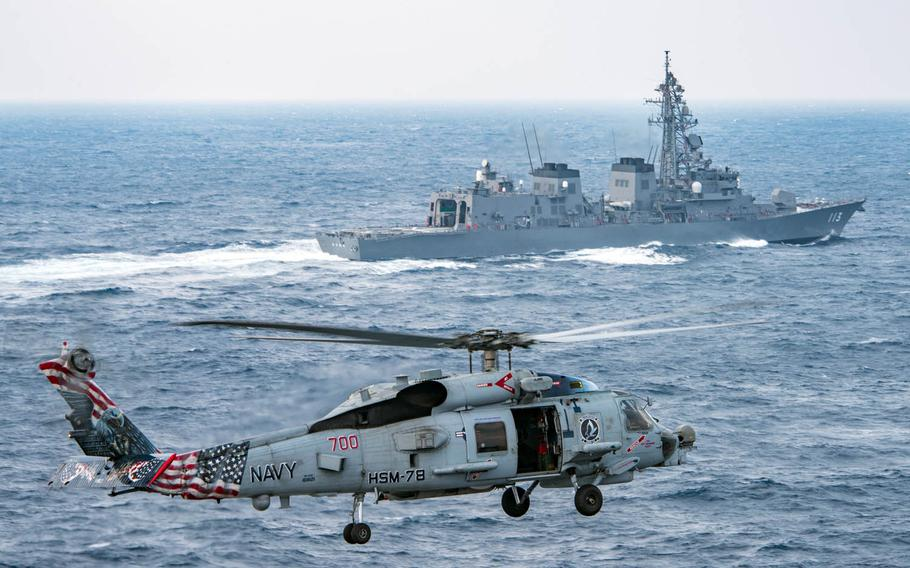 An MH-60R Sea Hawk from the Blue Hawks of Helicopter Maritime Strike Squadron 78 flies near the Japan Maritime Self-Defense Force destroyer JS Sazanami during drills Wednesday, March 8, 2017, in the East China Sea.