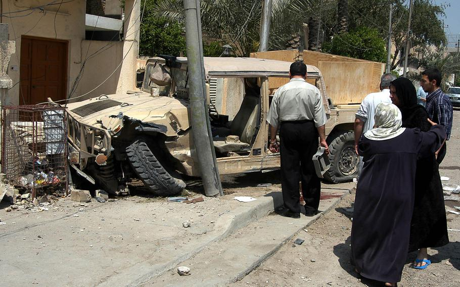 Bystanders look at a 1st Cavalry Division Humvee after it crashed in front of a house after being hit by an improvised explosive device in Baghdad, Tuesday, April 13, 2004. Melissa Stockwell, then a first lieutenant, lost her left leg in the attack. She went on to be a three-time paralympian, winning  the bronze medal in the paratriathlon at the 2016 Games in Rio de Janeiro.
