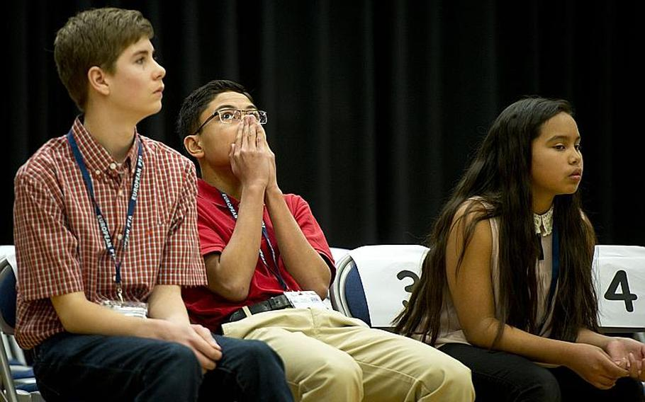 Naples Middle School's Ryan Rayos, center, anxiously listens to a competitor spell a word that could win Rayos the 35th annual European PTA Spelling Bee at Ramstein Air Base, Germany, on Saturday, March 18, 2017. Rayos went on to win in the 19th round.