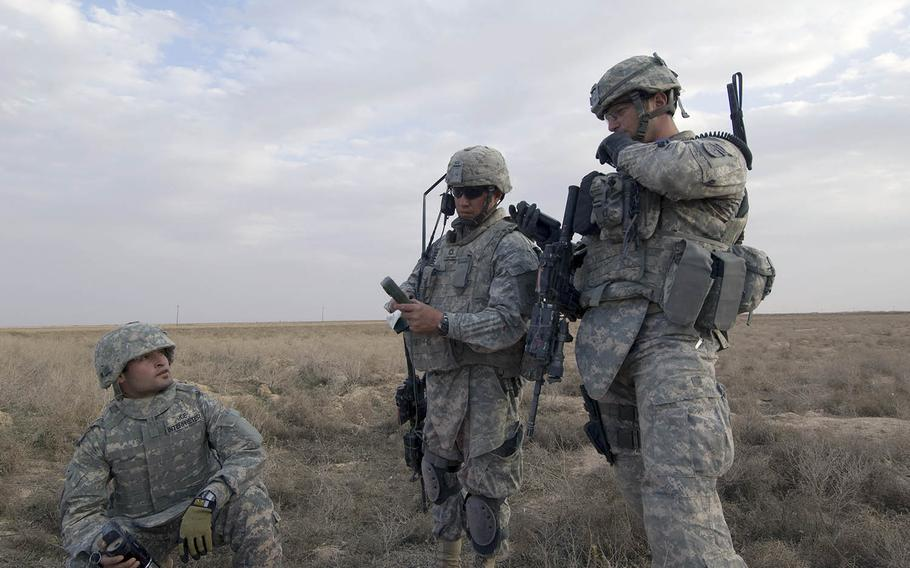 Soldiers coordinate an assault on a house suspected of hiding insurgents outside the village of Samood, in Diyala province, Iraq, on March 3, 2009.