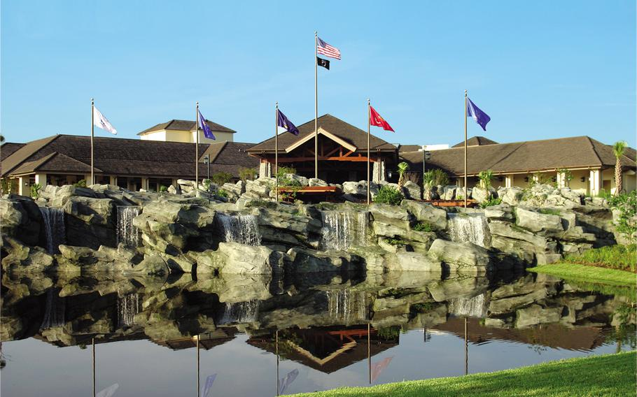 Atop an artificial rock formation, the flags of the Army, Navy, Air Force, Marines and Coast Guard flap in the breeze outside Shades of Green, a Department of Defense-owned resort for military members and their guests on the property of Walt Disney World. Inside, the clubhouse has a hunting-lodge feeling  with exposed roof beams, hewn stone and a fireplace.