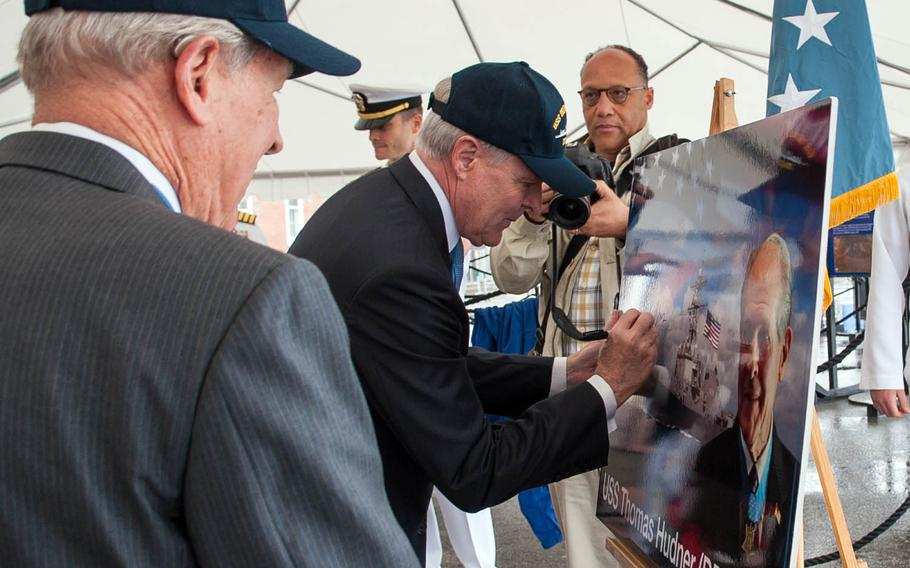 Then-Navy Secretary Ray Mabus signs an illustration of the guided-missile destroyer USS Thomas Hudner during a naming celebration in Charlestown, Mass., May 22, 2012.