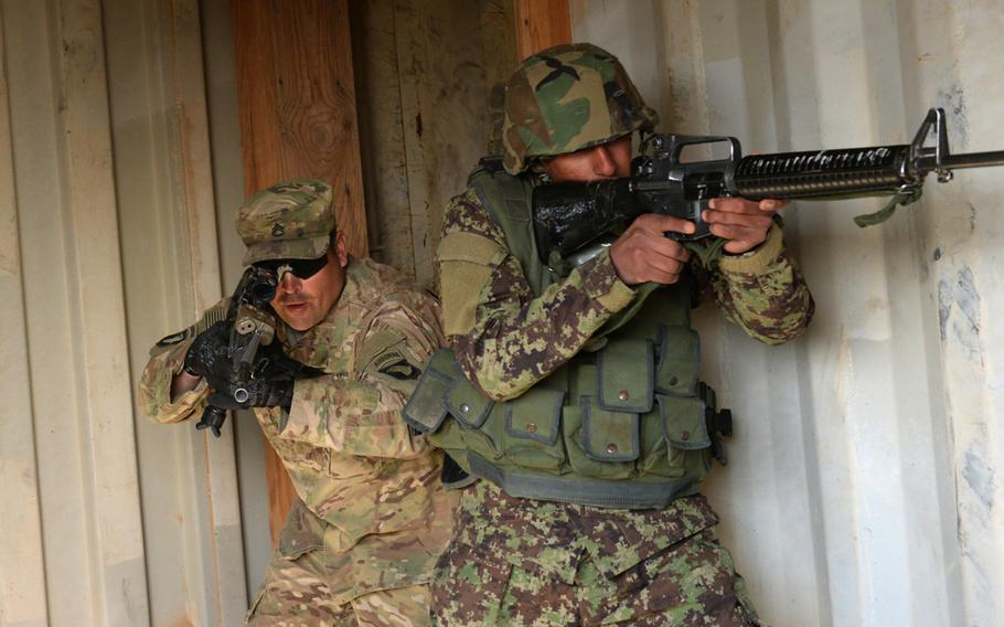 A U.S. Army adviser from Task Force Forge conducts a room clearing drill with an Afghan trainee to demonstrate proper tactial procedures at the Regional Military Training Center in Helmand Province, Afghanistan, March 8, 2017.