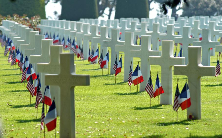 Rows of crosses and Stars of David stand in long rows at Normandy American Cemetery, Colleville-sur-Mer, France, decorated with American and French flags. The cemetery is the final resting place for 9,387 of our war dead. Visit one of the Memorial Day services at an American Battle Monuments Commission this Memorial Day weekend.