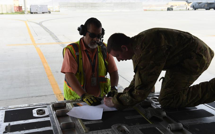 Senior Airman Ryan Berry, 26, of Bedford, Texas, right, checks a manifest at Bagram Air Field, May 4, 2017, before a C-130J flight to deliver supplies and passengers around Afghanistan.