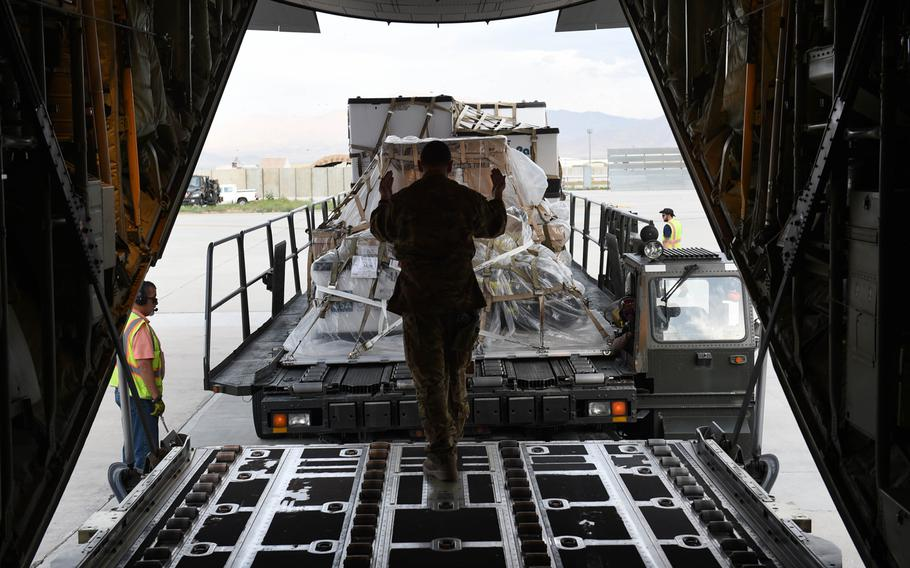 Senior Airman Ryan Berry, 26, of Bedford, Texas, right, loads cargo onto a C-130J at Bagram Air Field, Afghanistan, May 4, 2017.