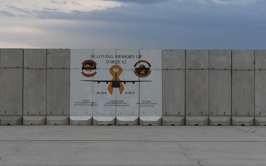 A T-Wall on the tarmac at Bagram Air Field, Afghanistan, displays a memorial to a C-130 flight and its crew.
