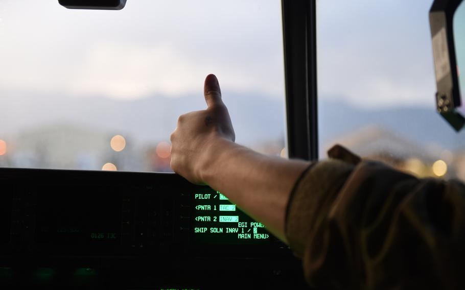 First Lt. Paul Harrington, 25, of Cumberland, R.I., signals to ground crews that his C-130J is ready to head to the runway, at Bagram Air Field, Afghanistan, May 4, 2017.