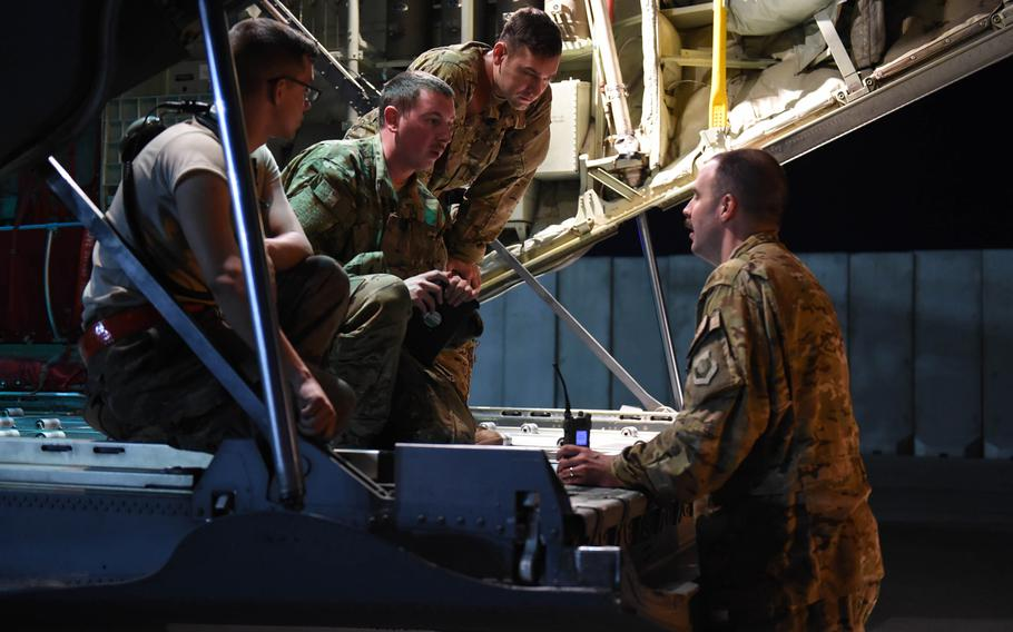 From left, Senior Airman Michael Bates, 22, of Athens, Ala., Senior Airman Ryan Berry, 26, of Bedford, Texas, and Capt. Brennan Wolford, 29, of Thornville, Ohio, confer with Master Sgt. John Beal, superintendent of the 774th Expeditionary Airlift Squadron, at Bagram Air Field, May 4, 2017.