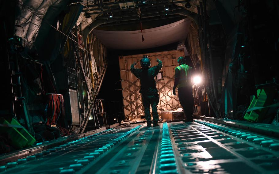 Senior Airman Ryan Berry, 26, of Bedford, Texas, waves a pallet onto a C-130J at Camp Dwyer, Afghanistan, May 5, 2017. Because Dwyer is less secure than Bagram or Kandahar, Berry must keep his body armor and helmet on when unloading and loading cargo.