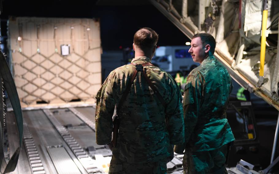 Maj. Timothy Fast, 34, of Baltimore, Ohio, the C-130J's pilot, and Senior Airman Ryan Berry, 26, of Bedford, Texas, the aircraft's loadmaster, await cargo at Kandahar Air Field, Afghanistan, May 5, 2017.