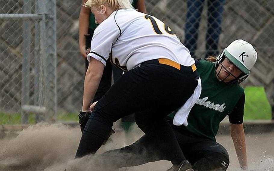 Kubasaki senior Reaven East, right, slides in under the tag of Kadena junior pitcher Lauren Erp during Thursday's Game 1 of the Okinawa district softball best-of-three finals. The Dragons won 17-9 and host Game 2 on Friday.