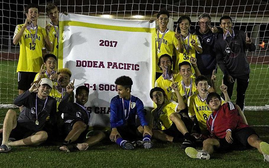 Kadena players  gather round the banner after their 1-0 win Wednesday over defending champion Kubasaki, the Panthers' third Far East Boys Division I Soccer Tournament title in five years.  MARY OBSUNA/SPECIAL TO STRIPES