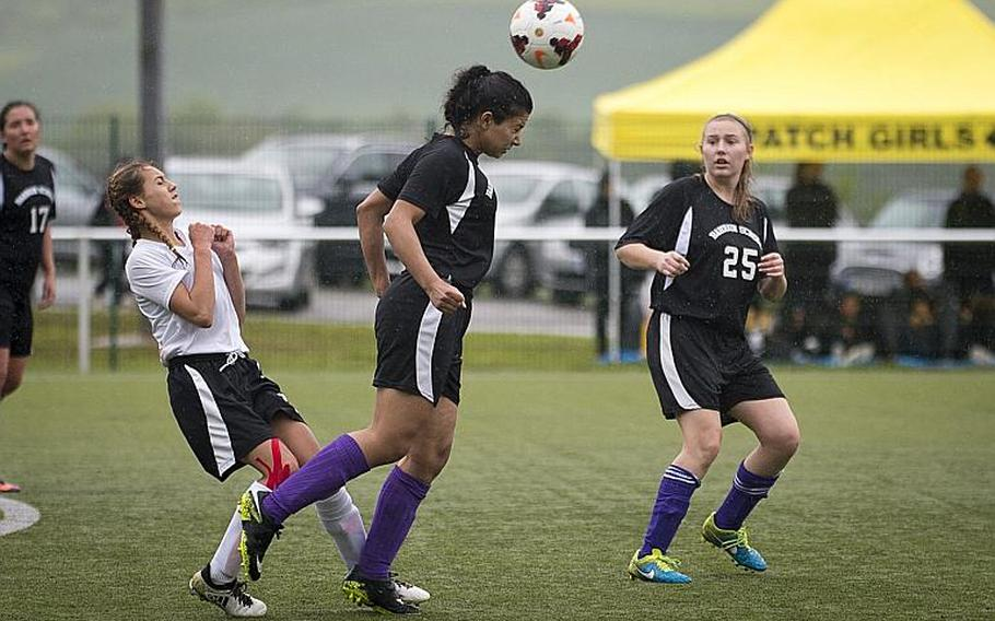 Bahrain's Asmaa Husseina, center, heads the ball away from AFNORTH's Kyla Kolosky as Helena Blaisdell-Black watches during the DODEA-Europe Division II semifinals in Reichenbach, Germany, on Friday, May 19, 2017. AFNORTH won the match 2-1 in double overtime.  MICHAEL B. KELLER/STARS AND STRIPES