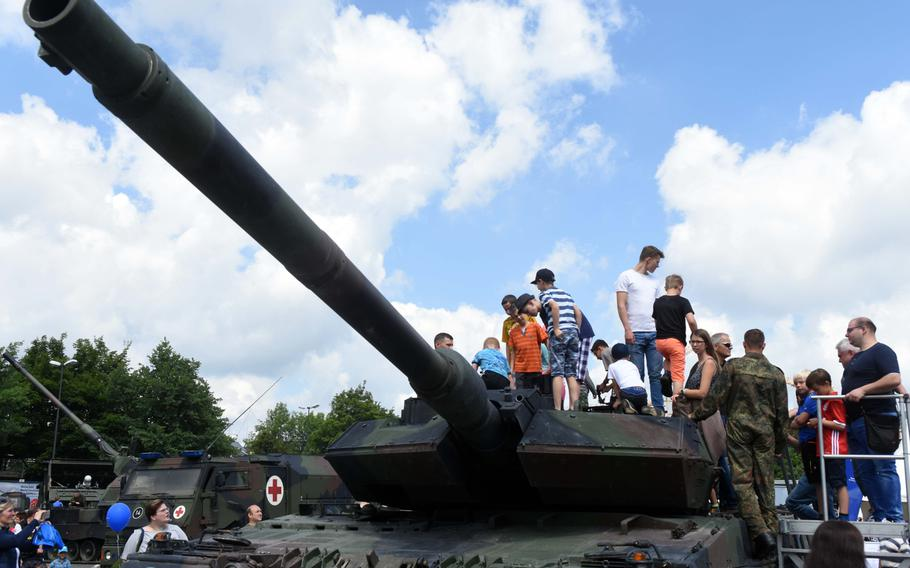 American and German children climb on top of a German Leopard II Main Battle Tank at the Day of the German Army, in Weiden, Germany, Saturday, June 10, 2017.