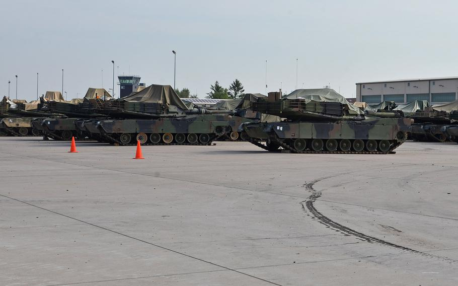 M1A1 Abrams tanks sit in the motor pool at Coleman Barracks in Mannheim, Germany, part of the Army prepositioned stocks operation. In the background is the air traffic control tower of the former Coleman Air Field.