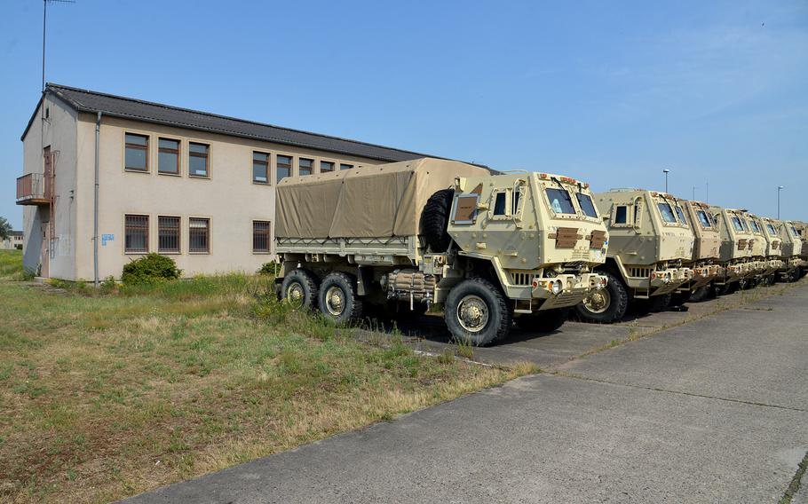 A row of  U.S. Army cargo trucks sit in front of one of the old buildings at Coleman Barracks in Mannheim, Germany. They are among the nearly 20,000 pieces of equipment being stored at the facility. The tan vehicles are being painted woodland green by the 405th Army Field Support Brigade, who oversee the operations at Coleman.