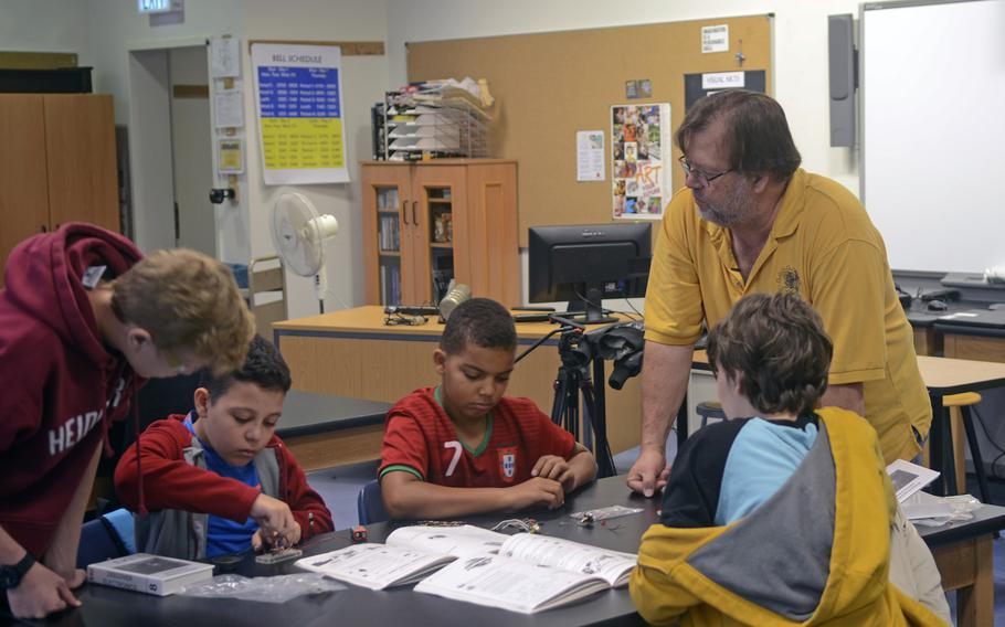 Frank Pendzich, a teacher and robotics club advisor at Wiesbaden High School, speaks to students as they work to assemble a circuitboard during a day camp at the school, Thursday, Aug. 10, 2017.