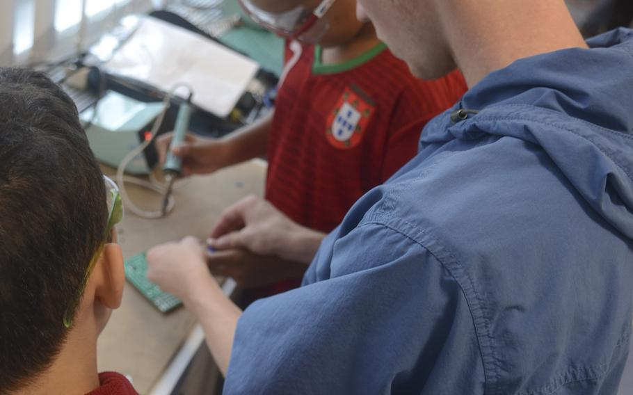 Parker Crumbly, a 2017 graduate of Wiesbaden High School, demonstrates to day campers how to manually solder a circuitboard at the science lab at the school, Thursday, Aug. 10, 2017.