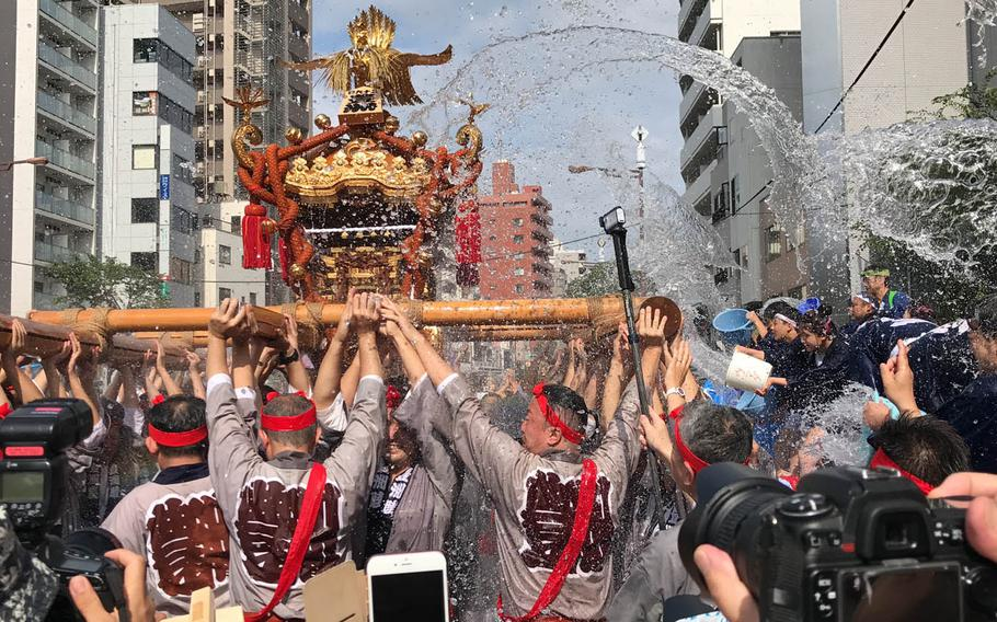 Parade participants are doused with water as they carry a portable Shinto shrine, called a mikoshi, through the streets of central Tokyo, Sunday, Aug. 13, 2017.