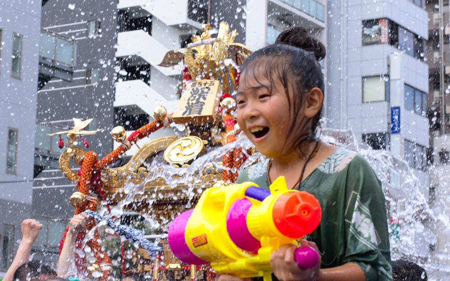 People carrying a miniature Shinto shrine called a mikoshi are drenched with water during the Fukagawa Hachiman Matsuri in Tokyo, Sunday, Aug. 13, 2017.