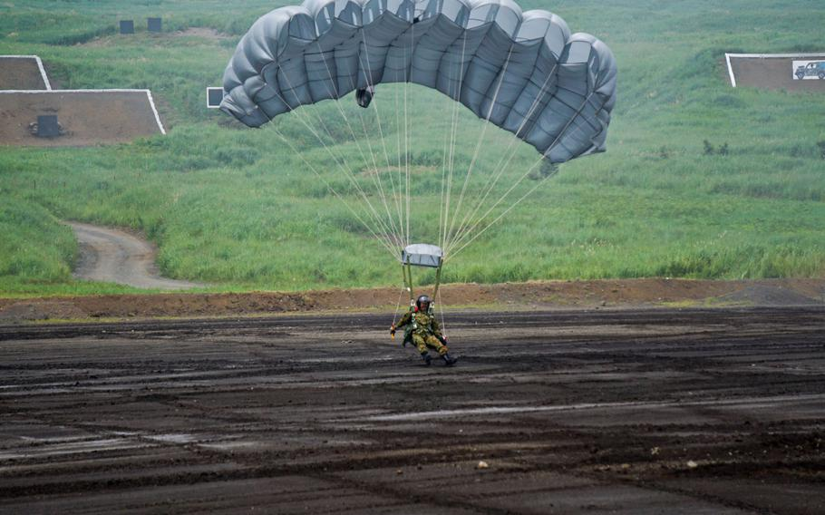A parachutist lands on a demonstration field after jumping from a Japan Ground Self-Defense Force CH-47 Chinook helicopter during Japan's annual Fuji Firepower demonstration near Mount Fuji, Japan, Thursday, Aug. 24, 2017.