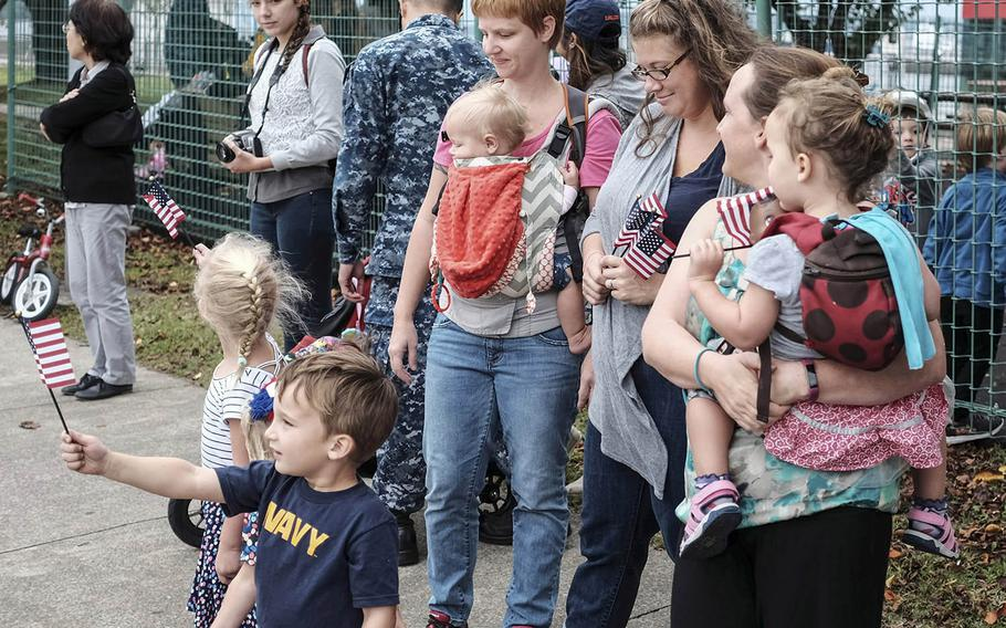 Children wave flags during a procession of USS John S. McCain sailors and their families ahead of a memorial ceremony at Yokosuka Naval Base, Japan, Wednesday, Oct. 4, 2017.