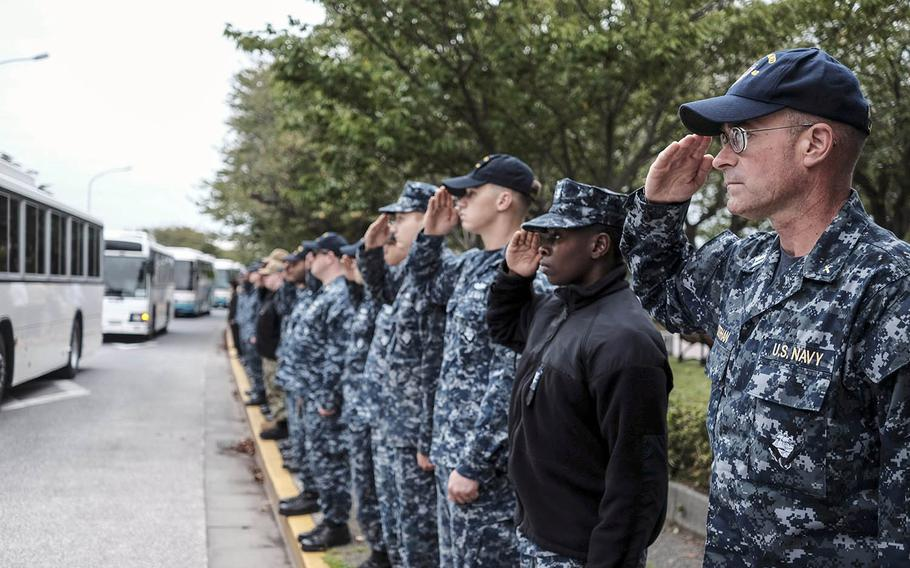 Servicemembers salute a procession of USS John S. McCain sailors and their families ahead of a memorial ceremony at Yokosuka Naval Base, Japan, Wednesday, Oct. 4, 2017.