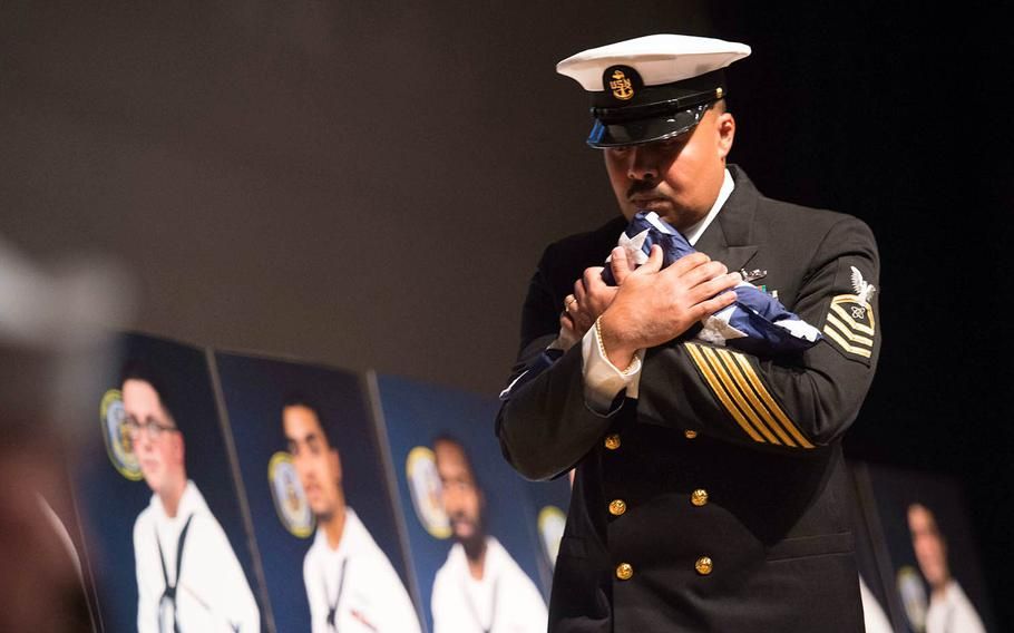 Chief Petty Officer Victor Grandados carries a folded flag to present to family members during the USS John S. McCain memorial service at Yokosuka Naval Base, Japan, Wednesday, Oct. 4., 2017.