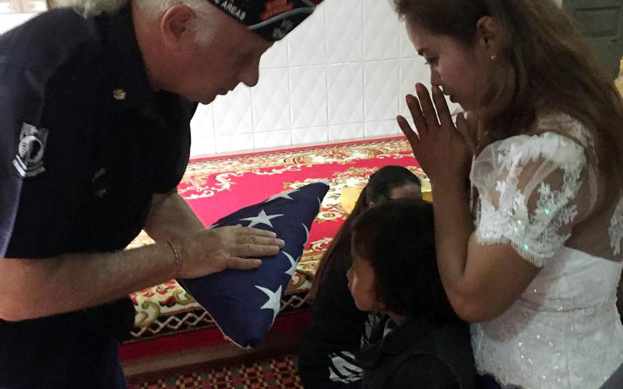 Kenneth Stein, commander of Veterans of Foreign Wars, Pacific Area, District V, presents an American flag to the family of deceased Air Force veteran Jimmie Herschal Sillavan during a funeral service in Phnom Penh, Cambodia, Sunday, Nov. 19, 2017.