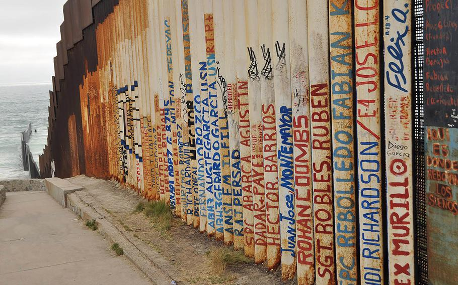 Graffiti on the fence demarcating the border between Tijuana, Mexico and San Diego, California that plunges into the Pacific Ocean, has been painted with the names of deported American veterans.