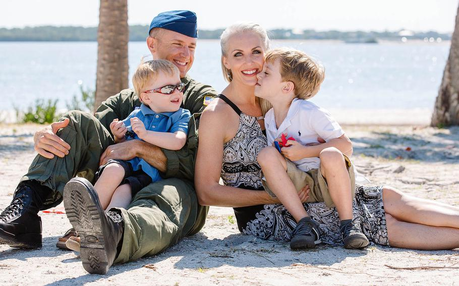 Coast Guard Petty Officer 1st Class James Nelson, left, holds his youngest son Coleman, and his wife Mary holds their middle son Wyatt, who is autistic, during a family moment in Clearwater, Florida in the spring of 2017. Mary Nelson said problems with Tricare following Jan. 1 changes have forced Wyatt's behavioral therapy center