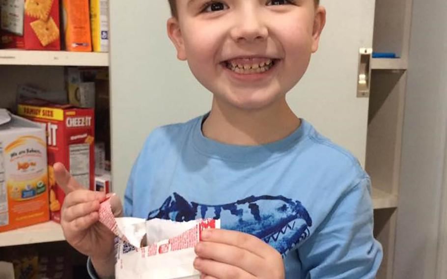 """Evan, 7, who has autism, beams after opening a package of muffins by himself for the first time. His mother Mandy Farmer, who writes a blog """"Motherhood,"""" says the therapy services for her son that helped him learn these skills, have been cut in half due to glitches in the Tricare overhaul on Jan. 1."""