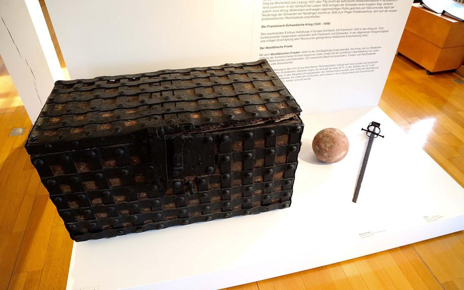 A chest, stone canon ball and sword on display in at the Theodor-Zink-Museum in Kaiserslautern, Germany. The chests were used to safeguard valuables and important deeds during fires and in times of war. The city has been destroyed and rebuilt no fewer than three times since the Middle Ages.